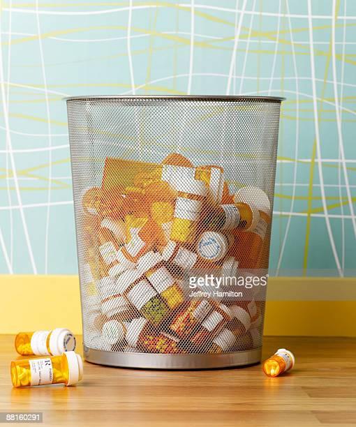 Prescription pill bottles in waste basket