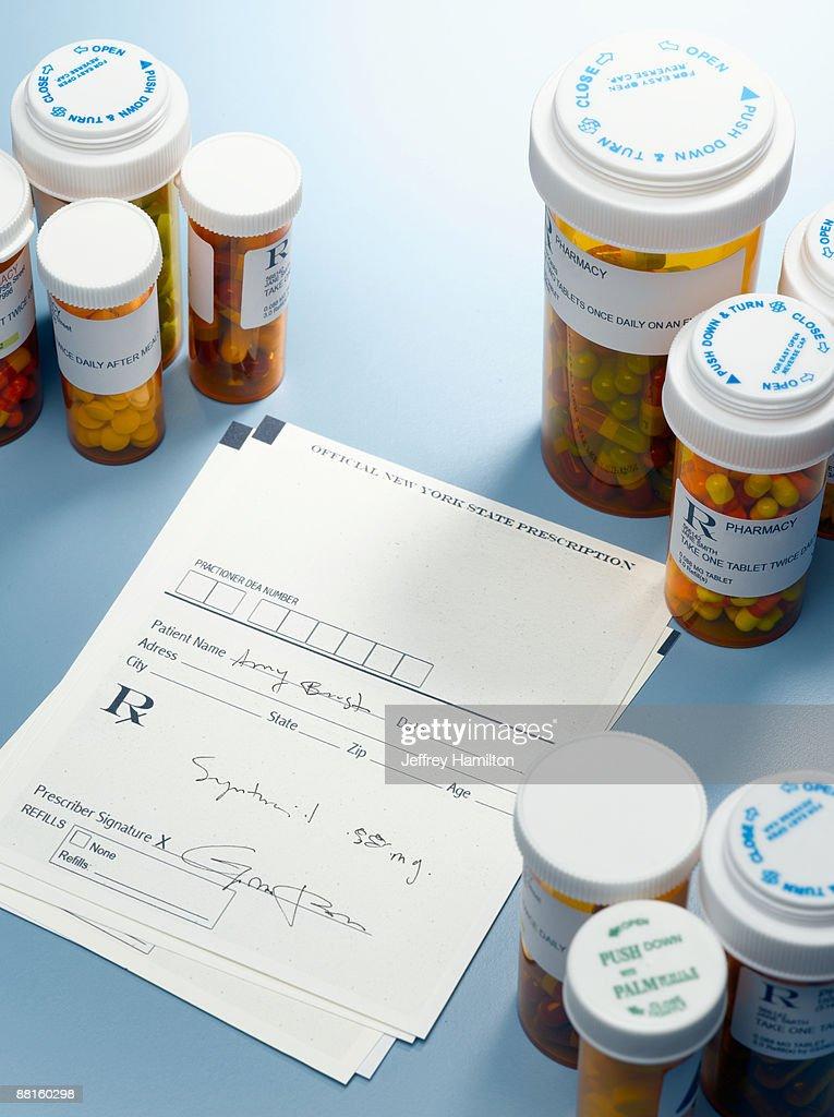 Prescription slip and pill bottles : Stock Photo
