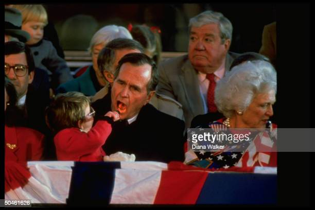 Preselect Bush getting his tonsils checked by grandchild Ellie LeBlond w Barbara Marilyn Quayle at inaugural fete at Lincoln Mem orial