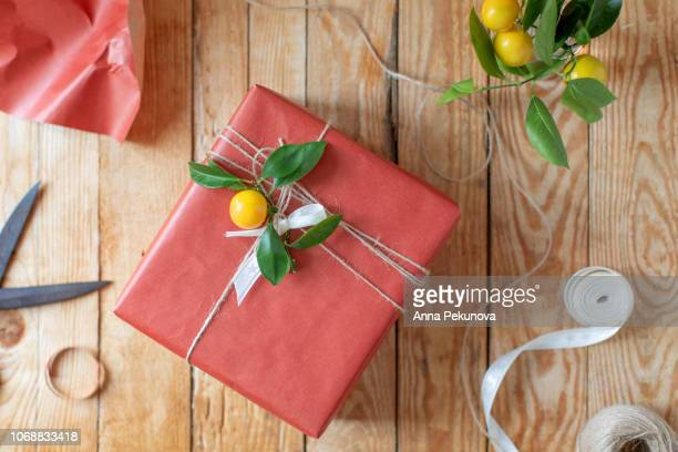 Present wrapped in red paper decorated with branch of mandarine tree