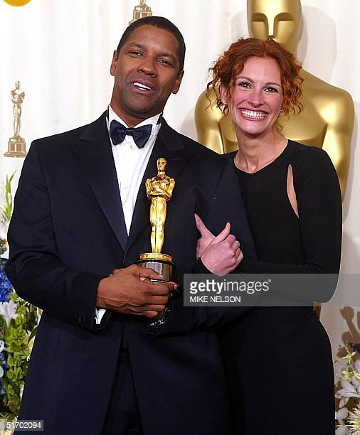 Presenter actress Julia Roberts poses with US actor Denzel Washington who holds his Oscar for best actor in a leading role for his portrayal of...