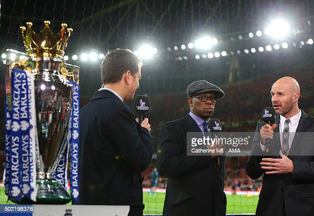 Presenter and former Arsenal player Ian Wright looks over towards the Barclays Premier League trophy as he reports pitch side for Sky with Danny...