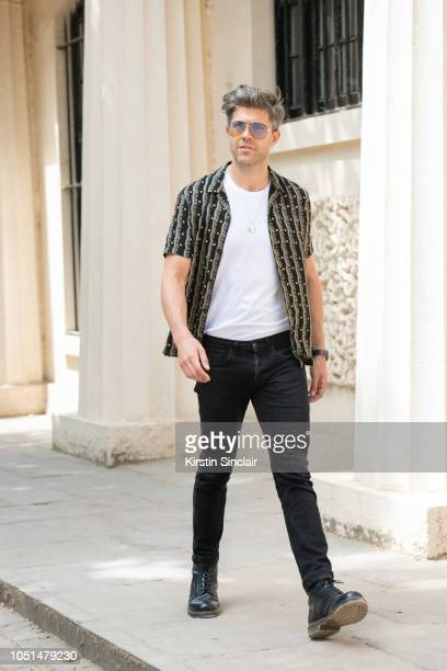 Presenter and Model Darren Kennedy wears Carrera sunglasses All Saints shirt Levi's T shirt and jeans Doc Martens boots during London Fashion Week...
