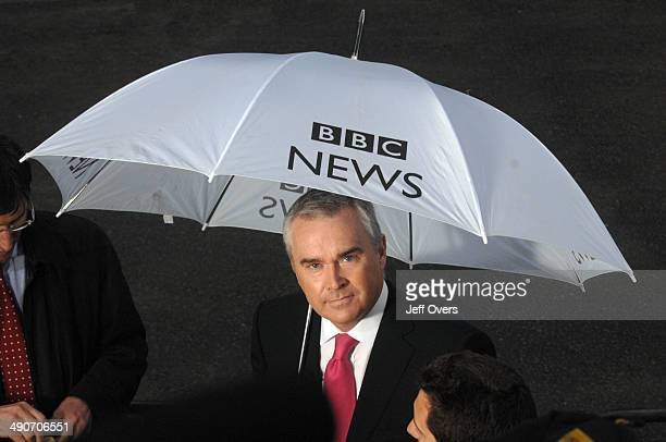 Presenter and newsreader Huw Edwards holds a BBC News umbrella as he reports from outside 10 Downing Street on the day that Gordon Brown took over...