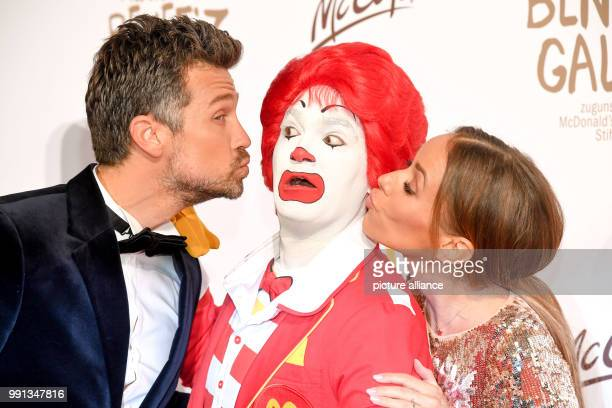 Presenter couple Wayne and Annemarie Carpendale kiss a Ronald McDonald impersonator at McDonald's benefit gala for children's aid in Munich Germany...