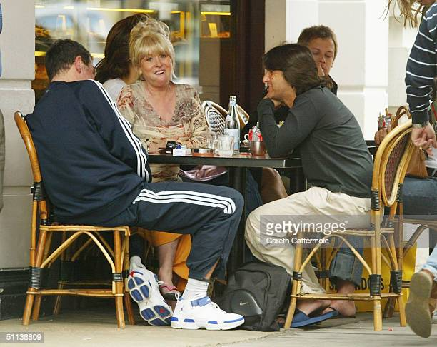 Presenter Dale Winton actress Barbara Windsor and an unidentified friend enjoy a drink together at a Marylebone High Street cafe on June 11 2004 in...