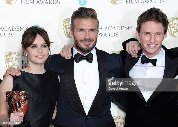 Presenter David Beckham poses with actors Felicity Jones and Eddie Redmayne in the winners room with the award for Outstanding British Film in 2015...