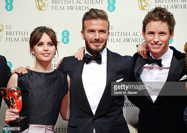 Presenter David Beckham poses with Felicity Jones and Eddie Redmayne with the Outstanding British Film award for The Theory Of Everything in the...