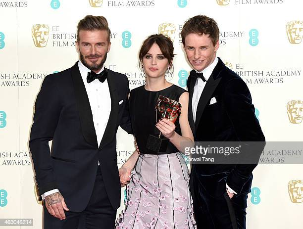 Presenter David Beckham poses with Felicity Jones and Eddie Redmayne with the Outstanding British Film award for 'The Theory Of Everything' in the...