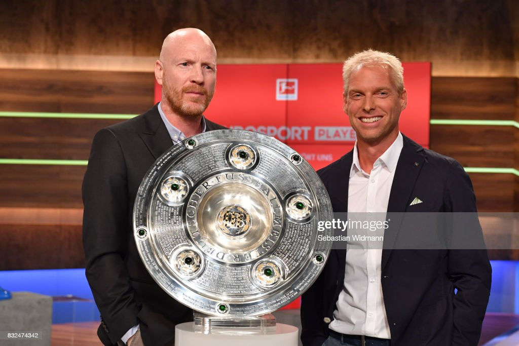 Presenter Jan Henkel (L) and Matthias Sammer laugh while posing for a picture during the Eurosport Bundesliga Media Day on August 16, 2017 in Unterfohring, Germany.