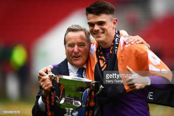 Presenter Jeff Stelling celebrates with Brad James of Hartlepool United and the Trophy following the Vanarama National League Play-Off Final match...