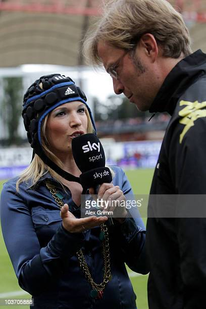 TV presenter Jessica Kastrop wears a helmet during her interview with head coach Juergen Klopp of Dortmund before the Bundesliga match between VfB...