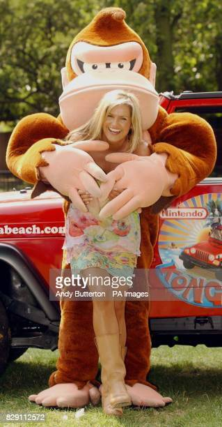 TV presenter Katy Hill is hugged by 'Donkey Kong' during a photocall to launch the Nintendo Konga Beach party at London Zoo in Regents Park central...