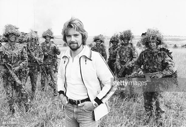 BBC presenter Noel Edmonds with a group of soldiers in camouflage whilst filming a television show on Salisbury Plains England 1976