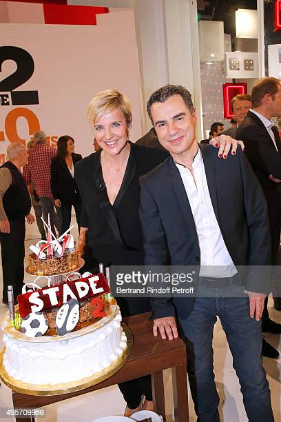 Presenter of Stade 2 Celine Geraud and Journalist Laurent Luyat pose in front of the Birthday Cake of the 'Stade 2' France 2 TV Chanel Sports Issue...