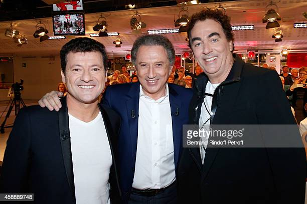 Presenter of the show Michel Drucker standing between Humorists 'Les Chevaliers du fiel' Francis Ginibre and Eric Carriere who present their movie...