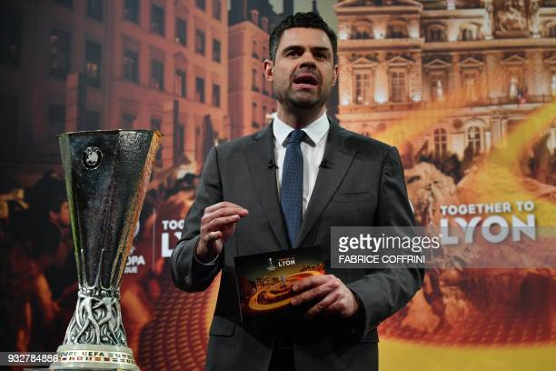 UEFA presenter Pedro Pinto gestures as he speaks next to the UEFA Europa League football cup during the draw for the quarter finals round of the UEFA...