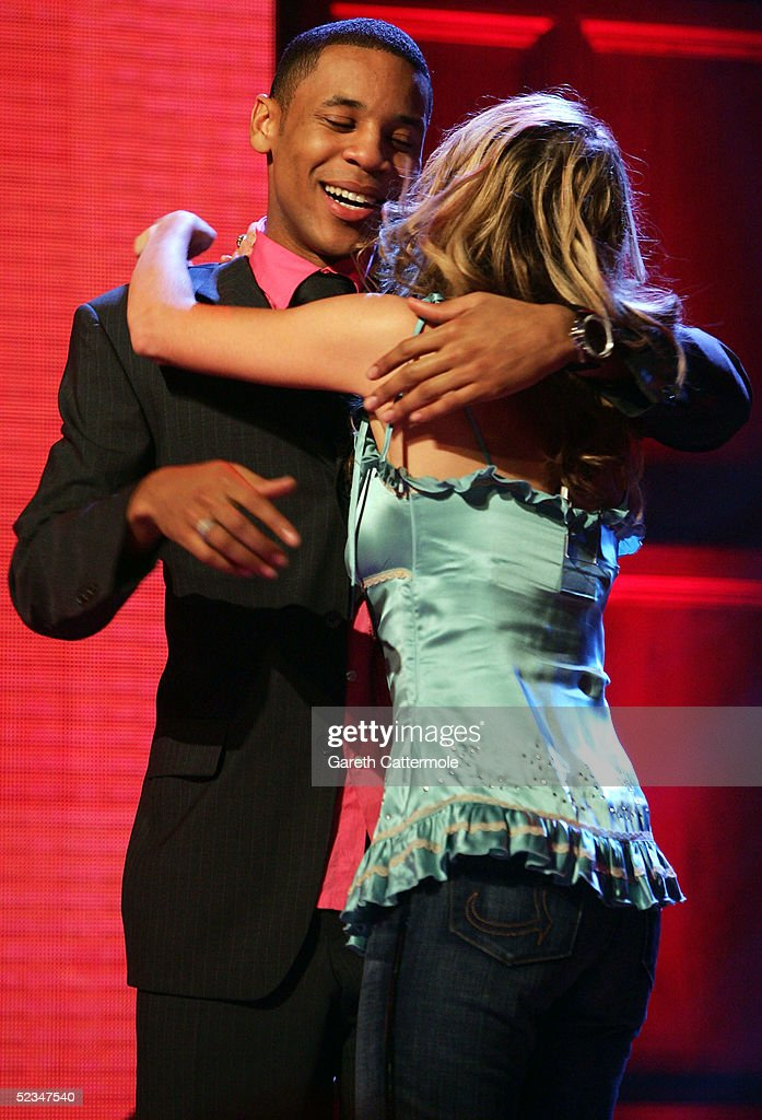 TV presenter Reggie Yates (L) and actress Debra Stephenson of 'Coronation Street' hug during the ninth eviction show for 'Comic Relief Does Fame Academy' at Lambeth College on March 9, 2005 in London. The new series sees 13 celebrities go head to head in the ultimate celebrity singing competition, with the grand final announcing the winner on March 11, Red Nose Day 2005.