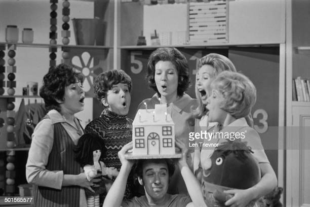 Presenter Rick Jones holds a birthday cake as his fellow presenters blow out the candles to celebrate the fifth birthday of the BBC TV children's...
