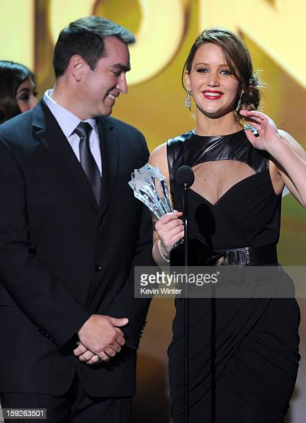 Presenter Rob Riggle looks on as actress Jennifer Lawrence accepts the Best Actress in an Action Movie Award for The Hunger Games onstage at the 18th...