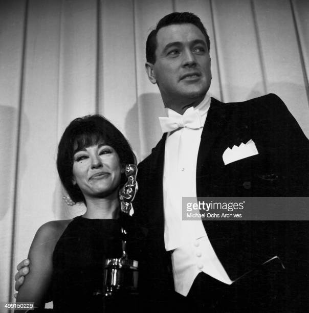 Presenter Rock Hudson poses with Rita Moreno and her Oscar during the 34th Academy Awards in Los AngelesCalifornia