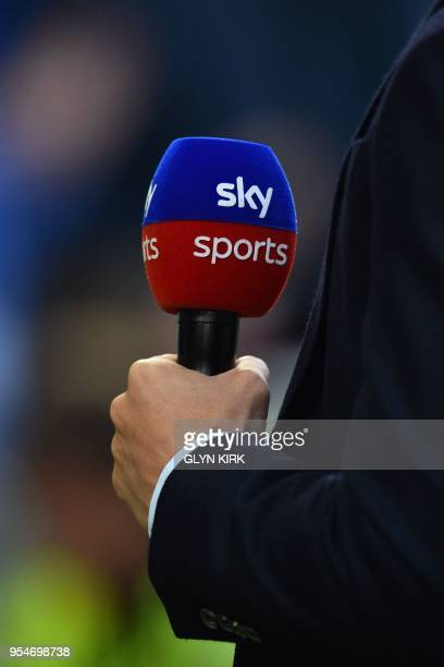 A presenter stands pitchside with a Sky sports microphone before the English Premier League football match between Brighton and Hove Albion and...