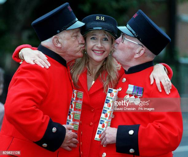 TV presenter Tania Bryer receives a kiss from Chelsea Pensioners Sid Towns and Fred Kibble at the launch of the Royal British Legion's scratchcard by...