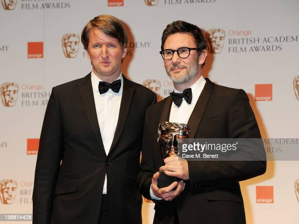 Presenter Tom Hooper and Michel Hazanavicius accepting the Best Cinematography Award on behalf of Guillaume Schiffman poses in the press room at the...