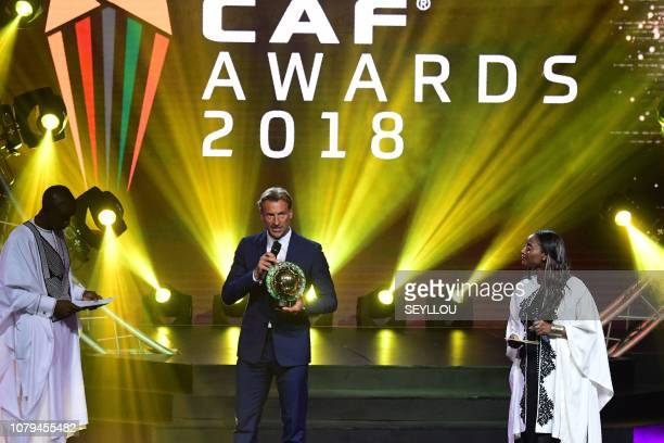 Presenters Aboubacry Ba and Aicha Cisse stand on stage with French soccer manager Herve Renard holding his trophy for CAF Men's coach of the year on...