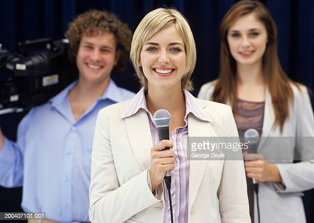 TV presenters and cameraman, smiling, portrait