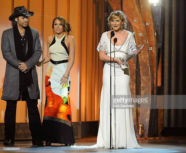 """Presenters Billy Ray Cyrus and Miley Cyrus present musician Jennifer Nettles with the award for """"Song of the Year"""" on stage during the 42nd Annual..."""