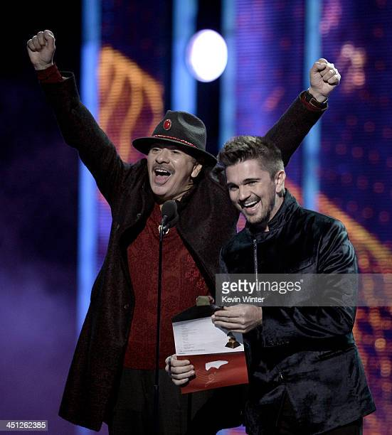 Presenters Carlos Santana and Juanes speak onstage during The 14th Annual Latin GRAMMY Awards at the Mandalay Bay Events Center on November 21 2013...