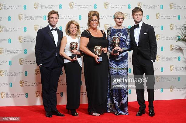 Presenters Douglas Booth Sam Claflin pose with Kathrine Gordon Lori McCoyBell and Evelyne Noraz winners of the MakeUp and Hair award in the winners...