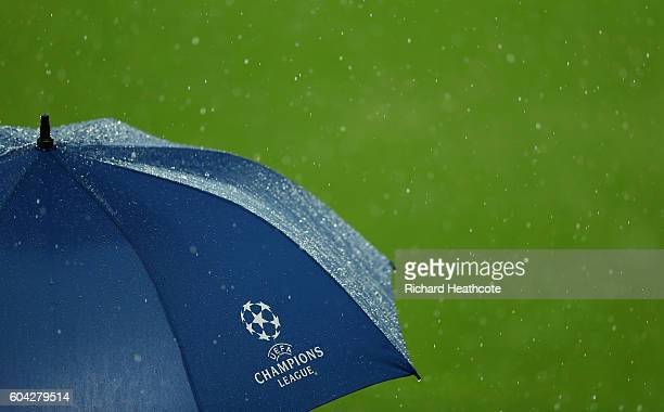 Presenters hide underneith an umbrella as rain falls during the UEFA Champions League Group A match between Manchester City FC and VfL Borussia...
