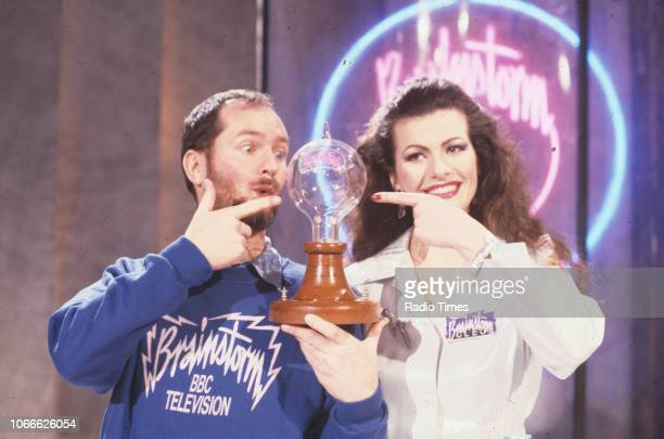 Presenters Kenny Everett and Cleo Rocos pictured holding a bulb on the set of the BBC television show 'Brainstorm' January 6th 1988