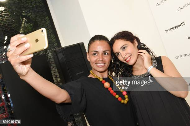 TV presenters Laurence Roustandjee and Aida Touihri pose for a elfie during Le Coq Sportif x Guerlain photocall at the Le Coq Sportif Flagship on May...