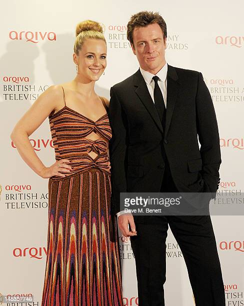 Presenters Miranda Raison and Toby Stephens pose in front of the winners boards at the Arqiva British Academy Television Awards 2012 held at Royal...