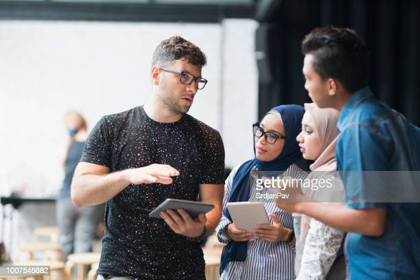 presenting new technologies - malay hijab stock photos and pictures