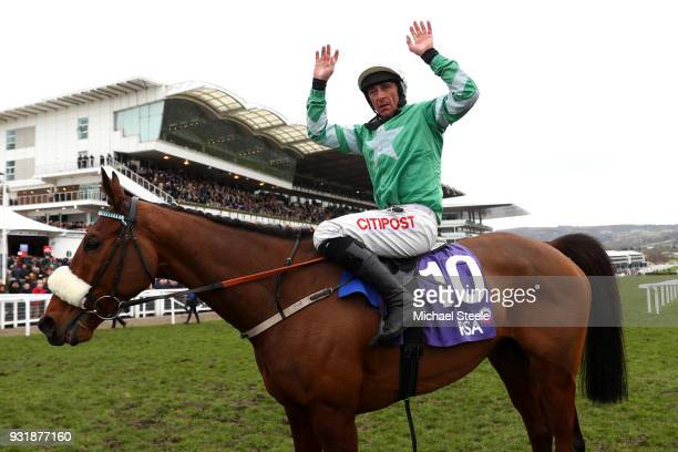 Presenting Percy ridden by Davy Russell celebrates winning the RSA Insurance Novices' Chase during Cheltenham Festival Ladies Day at Cheltenham...