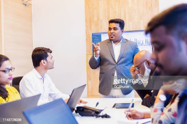 ceo presenting the annual profit and loss report in a board meeting - chairperson stock pictures, royalty-free photos & images