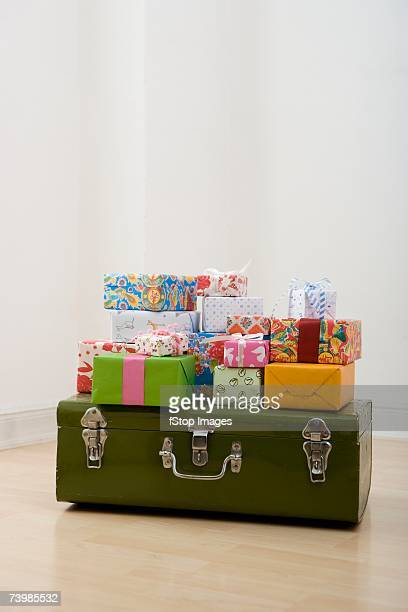 Presents stacked on top of a suitcase