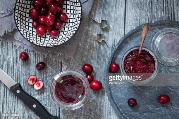 preserving glasses of cranberry jam and fresh cranberries - cranberry sauce stock photos and pictures