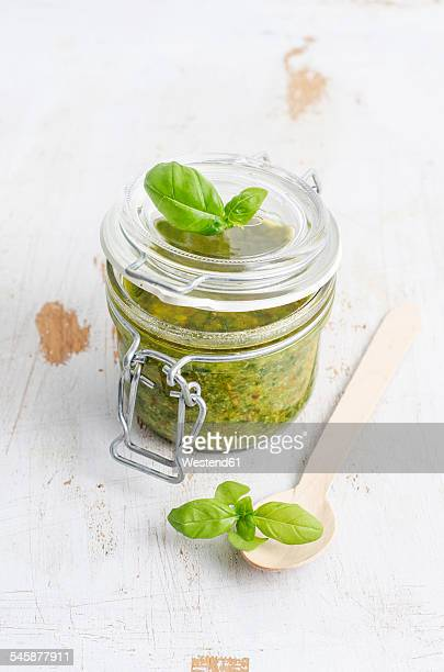 Preserving jar of fresh pesto, wooden spoon and basil leaves on white wood