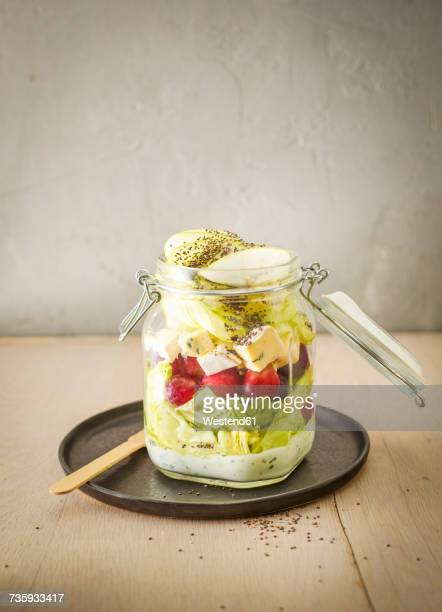 Preserving jar of iceberg salad with grapes, apple, blue cheese and chia seeds