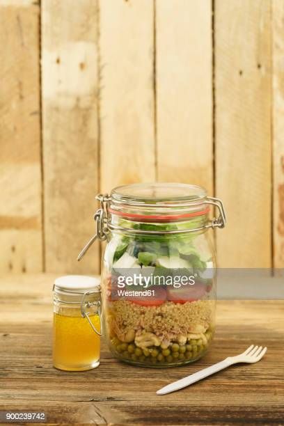 Preserving jar of mixed salad with peas, tuna, couscous, tomatoes, tuna, feta and jar of vinaigrette dressing