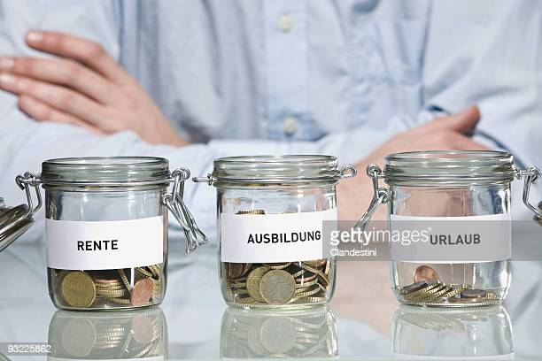 Preserving jars with Euro coins, Man in background