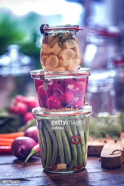 Bio-Knoblauch, Radieschen und grünen Bohnen in Gläsern konservieren