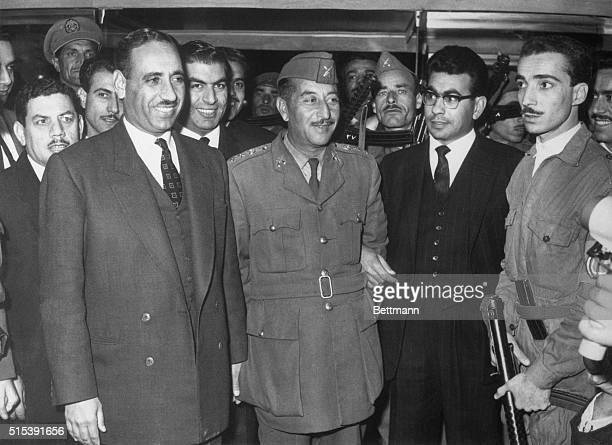 President Abdul Salam Arif head of the new Iraqi revolutionary regime poses with a group of his followers at Baghdad Hotel here recently after a news...