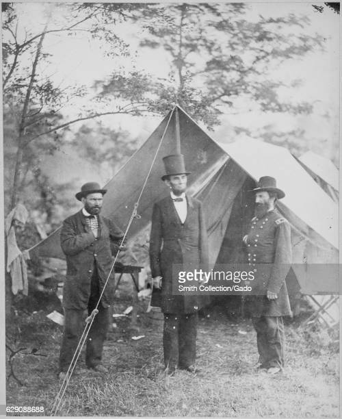 President Abraham Lincoln flanked by civil war officials standing outside of a tent 1863 Image courtesy National Archives