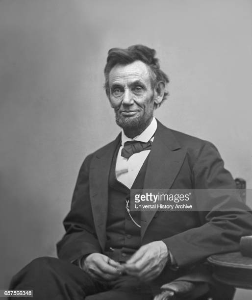 US President Abraham Lincoln Portrait Seated next to Table Holding Spectacles and Pencil Washington DC USA by Alexander Gardner February 1865